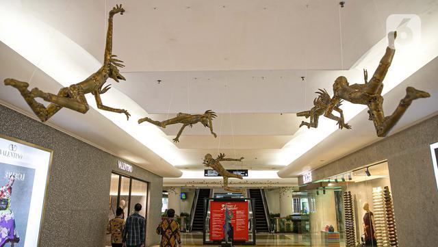 Pengunjung melintasi seni instalasi yang dipamerkan dalam pameran 'Seni yang Tidak Pernah Pudar' di Plaza Indonesia, Jakarta, Senin (15/3/2021). Sebanyak 43 karya dari 21 seniman tersebut merupakan rangkaian acara yang bertemakan '31 Years & Fabulous'. (Liputan6.com/Faizal Fanani)