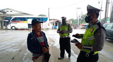 Aparat kepolisian memberikan masker gratis dan edukasi secara masif kepada para penumpang di pool bus Sinar Jaya, Jalan Inspeksi Kalimalang, Desa Suka Danau, Cikarang Barat, Kabupaten Bekasi, Jawa Barat