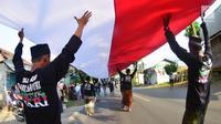 Sejumlah santri dari Pondok Pesantren Ashabul Kahfi membawa bendera Merah Putih besar saat mengikuti pawai Hari Santri Nasional 2017 di Gunungpati, Semarang (22/10). (Liputan6.com/Gholib)