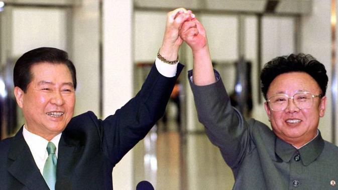 Presiden Korea Selatan, Kim Dae-jung dan pemimpin Korut Kim Jong-il berpegangan tangan sebelum menandatangani perjanjian di tengah pertemuan bersejarah antara dua Korea di Pyongyang pada 14 Juni 2000 (AFP-JIJI)