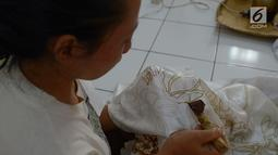 Warga melakukan proses pencantingan saat membuat kain batik di Rusun Rawa Bebek, Jakarta, Sabtu (6/7/2019). Kain dengan motif Jakarta dan motif lainnya ini dibuat oleh ibu-ibu penghuni rusun Rawa Bebek, mereka menjualnya dengan harga Rp1,5 hingga Rp 2,5 juta per kain. (merdeka.com/Imam Buhori)