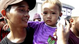 Seorang anak melakukan pengecekan suhu badan sebelum memasuki di Stadion Sport Center, Tangerang, Jumat (6/3/2020). Kegiatan tersebut untuk mengantisipasi maraknya isu penyebaran virus Corona. (Bola.com/M Iqbal Ichsan)