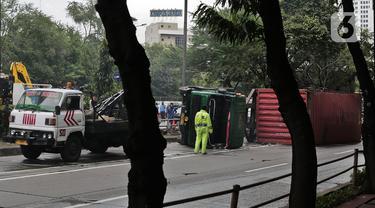 Petugas melakukan evakuasi Kontainer yang terguling di Jalan S Parman, Jakarta Barat, Senin (4/5/2020). Tidak ada korban jiwa dalam kecelakaan tersebut, namun kecelakaan tersebut membuat lalin dijalan itu terimbas kemacetan yang cukup panjang. (Liputan6.com/Johan Tallo)