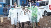 Petugas yang mengenakan APD membawa peti berisi jenazah dengan protokol COVID-19 di TPU Srengseng Sawah 2, Jakarta, Selasa (9/2/2021). Sudah lebih dari sepekan TPU Srengseng Sawah 2 menerima pemakaman korban COVID-19 dengan jumlah yang dimakamkan sehari maksimal 10 jenazah. (merdeka.com/Arie Basuki)