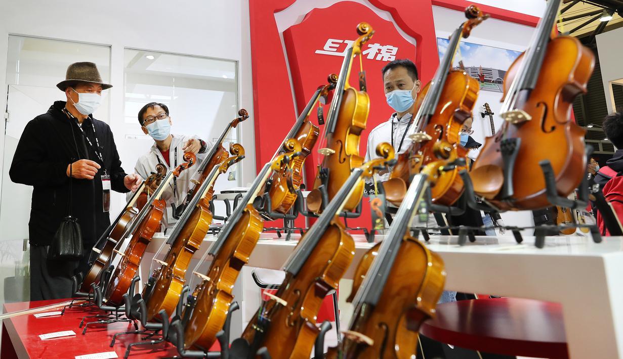 Seorang staf (kedua dari kiri) memperkenalkan biola kepada pengunjung pada ajang Music China 2020 di Shanghai New International Expo Center, China, 28 Oktober 2020. Music China 2020 diikuti lebih dari 1.000 industri musik dari 11 negara dan kawasan dengan produk-produk baru mereka. (Xinhua/Fang Zhe)