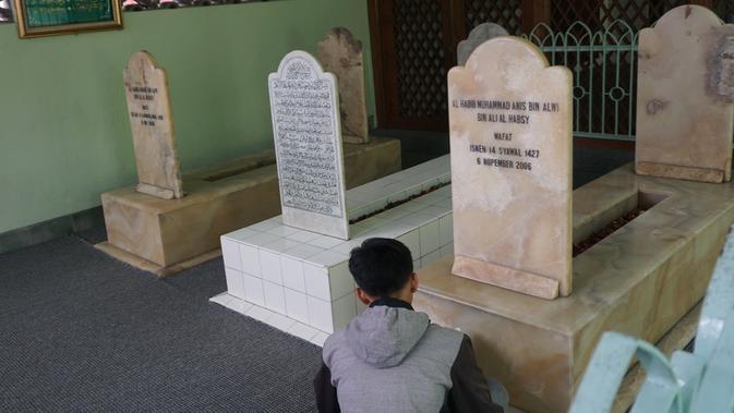 Seorang pengunjung sedang melakukan ziarah di makam putra dan cucu Habib Ali Al Habsyi di komplek Masjid Riyadh Solo.(Liputan6.com/Fajar Abrori)