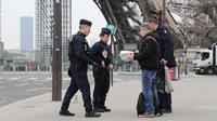 Polisi memeriksa dokumen warga saat lockdown di depan Menara Eiffel, Paris, Prancis, Rabu (18/3/2020). Prancis mengerahkan puluhan ribu polisi untuk berpatroli selama lockdown akibat virus corona COVID-19. (Ludovic MARIN/AFP)