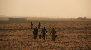Warga melarikan diri dengan berjalan kaki saat pasukan Turki memburu milisi Kurdi di Ras al Ayn, Suriah, Rabu (9/10/2019). Presiden Turki Recep Tayyip Erdogan mengumumkan dimulainya operasi militer terhadap milisi Kurdi di timur laut Suriah. (AP Photo/Baderkhan Ahmad)