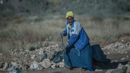 Seorang wanita lansia, Clara Maitse menggali tanah untuk mencari berlian di Kimberley, Northern Cape, Afrika Selatan (5/6). Hingga usia 77 tahun, Clara Maitse masih mencari berlian di bekas pertambangan ilegal. (AFP/Mujahid Safodien)