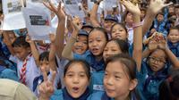 Para siswa tersenyum sambil memegang gambar tim sepak bola Thailand setelah berhasil diselamatkan dari dalam gua di Chiang Rai, Thailand, Rabu (11/7). (AFP Photo/Tang Chhin Sothy)