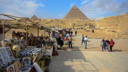 Sejumlah pedagang menjajakan dagangannya di dekat kompleks Piramida Giza di pinggiran Ibukota Kairo, Mesir (6/12). Piramida-piramida yang ditemukan disini adalah kategori terbesar dibandingkan dengan piramida yang ada di bumi.(AFP Photo/Mohamed El-Shahed)