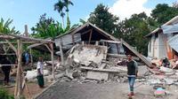 Penduduk desa berjalan di depan rumah yang roboh akibat gempa di desa Sajang, Sembalun, Lombok Timur, Minggu (29/7). Data sementara mencatat, gempa bumi tektonik 6.4 SR itu mengakibatkan 10 orang meninggal dunia dan puluhan rumah rusak. (AP/Rosidin)