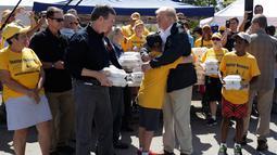 Presiden AS, Donald Trump memeluk seorang anak saat membantu membagikan makanan kepada korban badai Florence di Temple Baptist Church di New Bern, N.C. (19/9). (AP Photo/Evan Vucci)