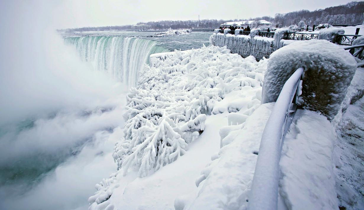 Pengunjung mengabadikan pemandangan Horseshoe Falls di Air Terjun Niagara yang membeku di Ontario, Kanada, Jumat (29/12). Cuaca dingin melanda sebagian besar wilayah utara Amerika Serikat di akhir tahun ini. (Aaron Lynett/Canadian Press via AP)