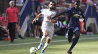 Penyerang Liverpool, Mohamed Salah, berebut bola dengan pemain Manchester United, Axel Tuanzebe, pada laga ICC 2018 di Stadion Ann Arbor, Michigan, Minggu (29/7/2018). Liverpool menang 4-1 atas Manchester United. (AP/Carlos Osorio)