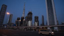 Sebuah taksi melintasi Jalan Sheikh Zayed 12 dekat Burj Khalifa, Dubai, Uni Emirat Arab, Minggu (5/4/2020). Pemerintah Dubai memberlakukan lockdown mulai 5 April 2020. (AP Photo/Jon Gambrell)