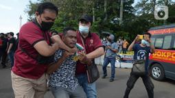 Aparat kepolisian mengamankan seorang pria saat unjuk rasa memperingati May Day atau Hari Buruh di kawasan Patung Kuda, Jakarta, Sabtu (1/5/2021). Polisi mengamankan sejumlah massa yang diduga mahasiswa dalam aksi unjuk rasa tersebut. (merdeka.com/Imam Buhori)
