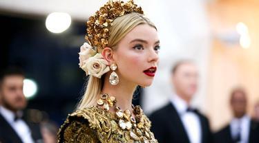 Anya Taylor-Joy sukses bikin publik terkesima saat hadiri Met Gala 2018 lalu. Ia tampil memesona dengan gaun Dolce & Gabbana berhias renda emas dengan hiasan kepala penuh bunga. (Liputan6.com/IG/@anyataylorjoy)