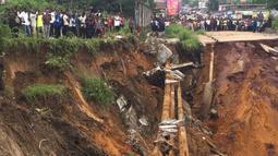 Warga melihat jalan ambruk oleh tanah longsor yang disebabkan hujan lebat melanda distrik Lemba, Kinshasa di Republik Demokratik Kongo pada Selasa (26/11/2019). Bencana tanah longsor ini juga telah melumpuhkan aktivitas warga dan lalu lintas. (AFP/Ange Kasongo)