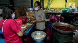 Petugas Taruna Siaga Bencana (Tagana) memotong tempe untuk dimasak di Dapur Umum Kementerian Sosial di GOR Otista, Jakarta, Minggu (21/2/2021). Dalam sehari, petugas menyiapkan hingga 6.000 paket nasi kotak yang didistribusikan ke 11 kelurahan terdampak banjir. (Liputan6.com/Faizal Fanani)