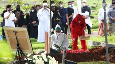 Suami presenter Rina Gunawan, Teddy Syach memandangi makam sang istri saat prosesi pemakaman di TPU Tanah Kusir, Jakarta, Rabu (3/3/2021). Rina Gunawan meninggal dunia di usia 46 tahun. (Kapanlagi.com/Budy Santoso)
