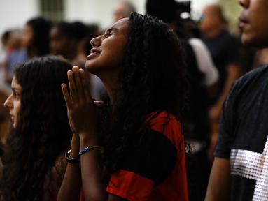 Seorang wanita berduka saat Misa peringatan untuk para korban kebakaran di akademi sepak bola Brasil, di Rio de Janeiro  (8/2). Kebakaran terjadi di kompleks latihan Flamengo pada Jumat (8/2/2019) pagi waktu setempat. (AP Photo/Leo Correa)