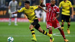 Gelandang Dortmund, Mahmoud Dahoud, melewat gelandang Bayern Munchen, Arturo Vidal, pada laga Piala Super Jerman di Stadion Signal Iduna Park, Dortmund, Sabtu (5/8/2017). Bayern Munchen menang adu penalti 5-4 atas Dortmund. (AFP/Patrik Stollarz)
