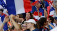 Suporter wanita mengibarkan bendera Prancis sebelum menyaksikan pertandingan melawan Norwegia pada grup A Piala Dunia Wanita 2019 di Stadion Nice, Prancis (12/6/2019). (AP Photo/Claude Paris)