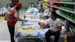 Sukarelawan memberikan buklet instruksi keselamatan kepada penduduk desa di tempat pengungsian sementara Sekolah Menengah No.168, Hefei, Provinsi Anhui, China, Rabu (29/7/2020). Lebih dari 300 penduduk desa di Kota Sanhe, Hefei, dievakuasi ke sekolah itu akibat terdampak banjir. (Xinhua/Liu Junxi)