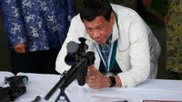 Presiden Filipina Rodrigo Duterte mencoba senapan sniper CS / LR4A buatan China di Clark Airbase di Filipina (28/6). Bantuan militer tersebut akan digunakan untuk melawan ancaman terorisme dan pembajakan dari kelompok militan. (AP Photo/Bullit Marquez)