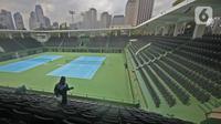 Petugas menyemprotkan cairan disinfektan pada bangku penonton di Lapangan Tennis Outdoor, Kompleks Olahraga GBK (Gelora Bung Karno), Senayan, Jakarta, Kamis (19/3/2020). Penyemprotan untuk mencegah penyebaran Virus Corona Covid-19 di Lingkungan Kompleks Olahraga GBK. (Liputan6.com/Herman Zakharia)