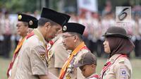 Presiden Joko Widodo memberi tanda kehormatan kepada seorang anak saat perayaan hari jadi Pramuka yang ke-57 di Lapangan Gajah Mada, Wiladatika, Cibubur, Jakarta, Selasa (14/8). (Liputan6.com/Faizal Fanani)
