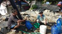 Korban gempa Palu menikmati air bersih melalui pipa PDAM yang bocor. (Liputan6.com