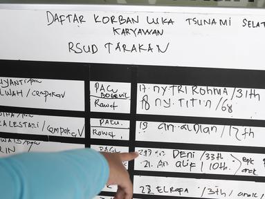 Daftar korban luka tsunami Selat Sunda karyawan RSUD Tarakan terpampang di RSUD Tarakan, Jakarta, Selasa (24/12). Dirut RSUD Tarakan Dian Ekawati mengatakan 54 anggota rombongan wisata RSUD Tarakan menjadi korban tsunami. (Liputan6.com/Herman Zakharia)