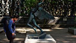 """Seorang pria melihat patung """" Angel of Triumph """" saat pameran """"Salvador Dali: Urban Dreams"""" di Mexico City, Selasa (14/3). Patung-patung tersebut adalah karya seniman asal spanyol yang bernama Salvador Dali. (AFP PHOTO / RONALDO SCHEMIDT)"""