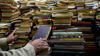 Jose Alberto Gutierrez memeriksa buku koleksinya yang ada di perpustakaan rumahnya di Bogota, 18 Mei 2017. Koleksi buku Gutierrez beragam, mulai dari buku-buku pelajaran hingga novel karya maestro Kolombia, gabriel Garcia Marquez. (GUILLERMO LEGARIA/AFP)