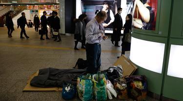 Seorang tunawisma Toshihiro Masuda (59) mengganti pakaian tidur di Stasiun Shinjuku, Tokyo, Jepang, Kamis (9/1/2020). Puluhan tunawisma tidur nyenyak di stasiun kereta bawah tanah Tokyo. (AP Photo/Jae C. Hong)
