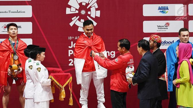 Presiden Joko Widodo memberikan mendali emas kepada atlet angkat besi Indonesia Eko Yuli Irawan setelah berhasil memenangkan pertandingan Angkat Besi pada  Asian Games 2018 di JIexpo, Kemayoran,Jakarta, Selasa (21/8). (merdeka.com/Imam Buhori)