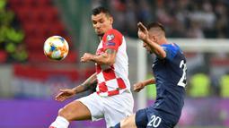 Bek Kroasia, Dejan Lovren, berebut bola dengan gelandang Slowakia, Robert Mak, pada laga Kualifikasi Piala Eropa 2020 di Trnava, Jumat (6/9). Slowakia kalah 0-4 dari Kroasia. (AFP/Joe Klamar)
