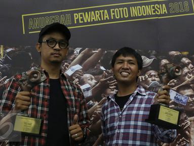 Juara 2 Kategori Spot News pewarta foto Liputan6.com, Faizal Fanani (kiri) dan juara 1 Kategori General News, Immanuel Antonius berpose memegang trofi Anugerah Pewarta Foto Indonesia (APFI) ke-VI di Bandung, Sabtu (9/4). (Liputan6.com/Immanuel Antonius)