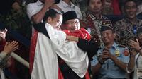 Presiden RI, Joko Widodo dan Ketua Umum IPSI, Prabowo Subianto, berpelukan dengan peraih medali emas pencak silat, Hanifan Yudani di Padepokan Pencak Silat TMII, Jakarta, Rabu (29/8). ANTARA FOTO/Kumparan/INASGOC/Aditia Noviansyah/pras/18