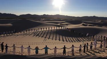 Peserta menghadiri kelas yoga yang diselenggarakan oleh komunitas YSYoga System di gurun Samalayuca, negara bagian Chihuahua, Meksiko pada 25 Mei 2019. Kelas yoga di padang pasir Samalayuca diselenggarakan setiap tahun, dan pesertanya semakin lama semakin bertambah banyak. (Herika MARTINEZ/AFP)
