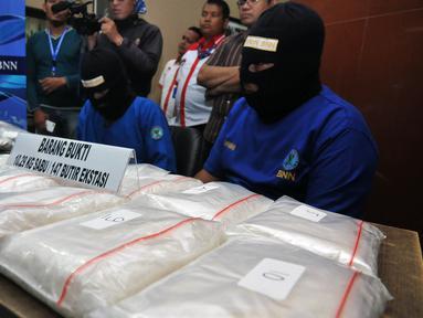 Badan Narkotika Nasional (BNN) menggelar barang bukti dan tersangka penyelundupan narkotika asal Malaysia, Jakarta, Rabu (17/6/2015). BNN mengamankan dua tersangka beserta barang bukti 10.293,96 sabu dan 147 butir ekstasi. (Liputan6.com/Johan Tallo)