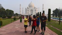 Turis mengabadikan foto saat mengunjungi Taj Mahal di Agra, India pada Senin (21/9/2020). Taj Mahal kembali dibuka untuk umum dalam gerakan simbolis seperti biasa, bahkan ketika India tampaknya akan mengambil alih AS sebagai pemimpin global dalam infeksi Virus Corona COVID-19. (Sajjad HUSSAIN/AFP)