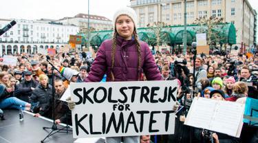 Aktivis iklim asal Swedia, Greta Thunberg memegang poster protes saat berunjuk rasa di Hamburg, Jerman, Jumat (1/3). Aksi 'Fridays for Future' ini diikuti oleh ribuan pelajar yang bolos sekolah. (Daniel Reinhardt/dpa via AP)