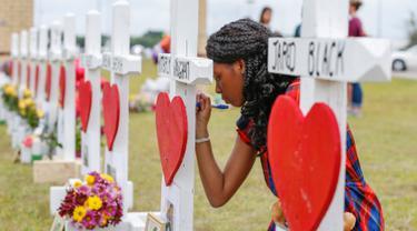 Siswi SMA Santa Fe, Jai Gillard menulis pesan pada salib di depan sekolah mereka di Texas, Amerika Serikat, Senin (21/5). Penembakan di sekolah Santa Fe beberapa waktu lalu menewaskan 10 orang. (Steve Gonzales/Houston Chronicle via AP)