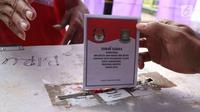Pemilih memasukkan surat suara setelah mencoblos pada Pilkada Serentak 2018 di TPS 29 Gandasari, Kota Tangerang, Rabu (27/6). Di TPS ini warga yang memilih untuk Pilkada Kota Tangerang dapat merasakan sensasi Piala Dunia 2018 (Liputan6.com/Angga Yuniar)