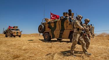 Pasukan AS berjalan melewati kendaraan militer Turki saat patroli gabungan di Desa al-Hashisha, Tal Abyad, Suriah, Minggu (8/9/2019). AS dan Turki patroli gabungan di Suriah timur laut untuk meredakan ketegangan Ankara dengan pasukan Kurdi yang didukung AS dalam memerangi ISIS. (DELIL SOULEIMAN/AFP)