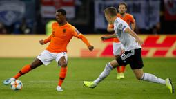 Gelandang Belanda, Georginio Wijnaldum, berusaha melewati bek Jerman, Matthias Ginter, pada laga Kualifikasi Piala Dunia 2022 di Hamburg, Jumat (6/9). Jerman kalah 2-4 dari Belanda. (AFP/Patrik Stollarz)