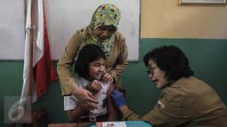 Seorang anak mengikuti kegiatan Bulan Imunisasi Anak sekolah (BIAS) di SDN 11 Pagi, Lubang Buaya, Jakarta, Selasa (4/10). Kegiatan ini untuk mewujudkan Indonesia bebas dari kanker serviks. (Liputan6.com/Faizal Fanani)